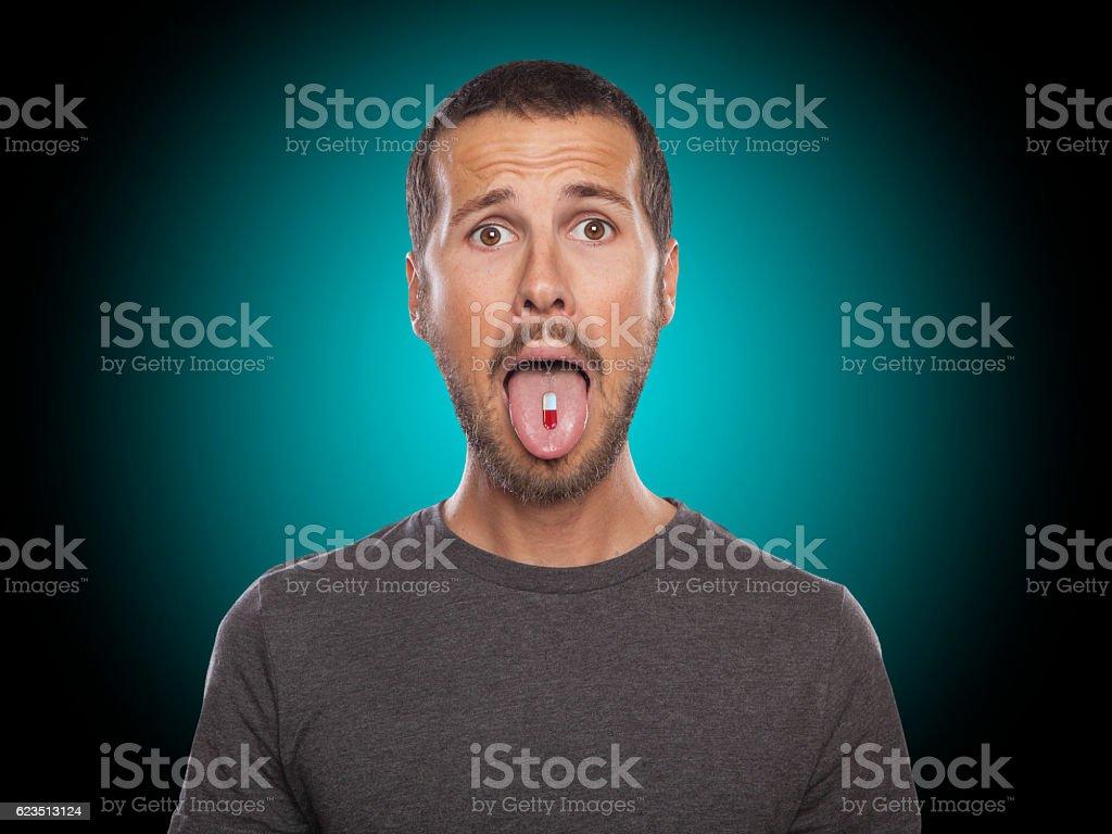 Porträt eines jungen Mannes, der eine Pille nimmt - Lizenzfrei Männer Stock-Foto