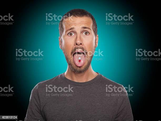 Porträt Eines Jungen Mannes Der Eine Pille Nimmt Stockfoto und mehr Bilder von Männer