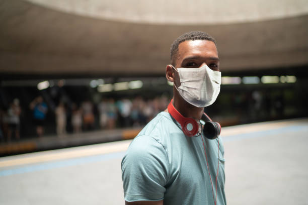 Portrait of a young man using protective mask at metro station stock photo