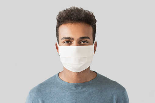 Masked man patient isolated on a gray background, copy space. Epidemic, pandemic, corona virus protection, healthy lifestyle, people concept
