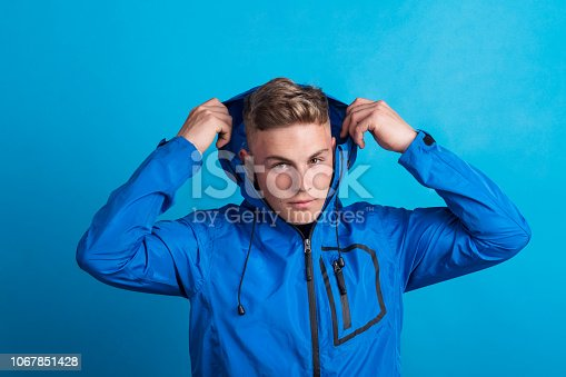 Portrait of a young handsome man with blue anorak in a studio, putting a hood on head. Copy space.
