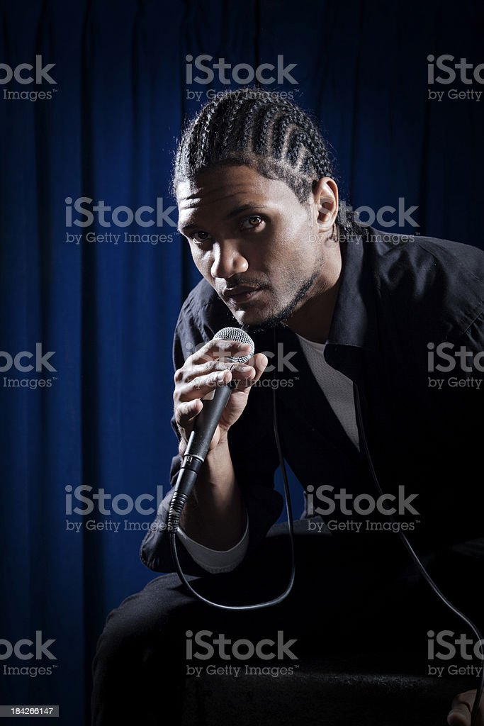 Portrait of a young man with microphone on stage royalty-free stock photo
