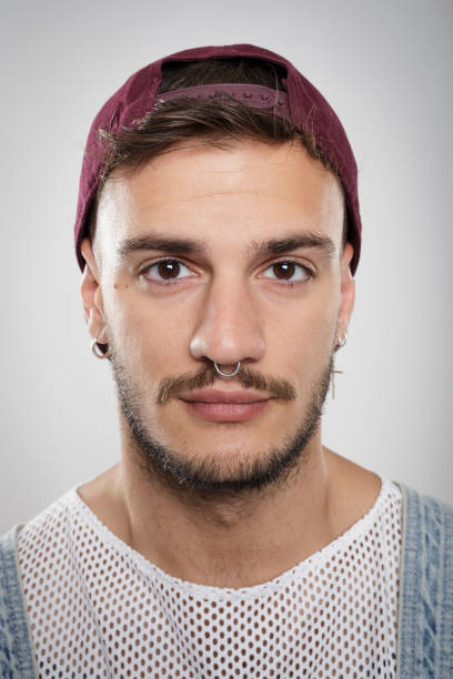Portrait of a young man with piercings and earrings against neutral background stock photo