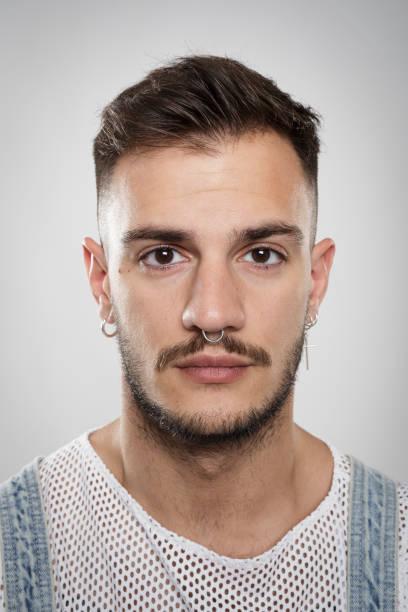 porträt eines jungen mannes mit piercings und ohrringe vor neutralem hintergrund - ohrringe piercing stock-fotos und bilder
