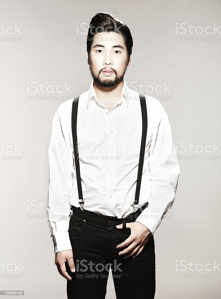 Portrait of a young man with suspenders looking at camera stock photo