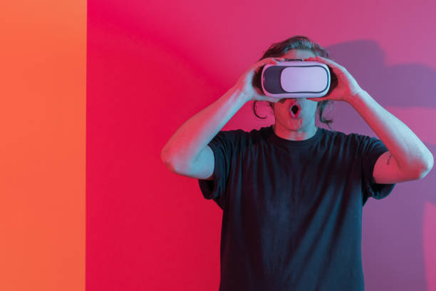 portrait of a young man with vr headset experience - vr red background imagens e fotografias de stock