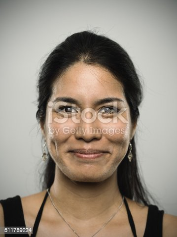 Studio portrait of a mixed race young woman looking at camera with happy expression. The woman has around 30 years and has long hair and wears earrings and a necklace. Vertical color image from a medium format digital camera. Sharp focus on eyes.