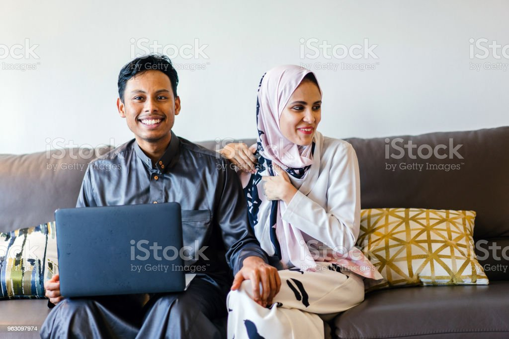 A Portrait Of A Young Muslim Married Couple Sitting On Their