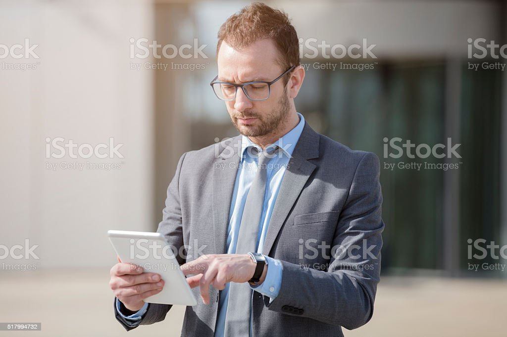 Portrait of a young professional using tablet device outdoors stock photo