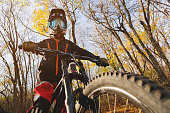 Portrait of a young rider in full protection of a full face helmet mask and gloves on a bicycle in an autumn forest with yellow leaves. The concept of involving young people in outdoor sports