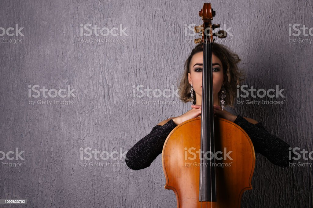 Portrait of a young sad woman. Part of the face is covered by the neck of the cello stock photo