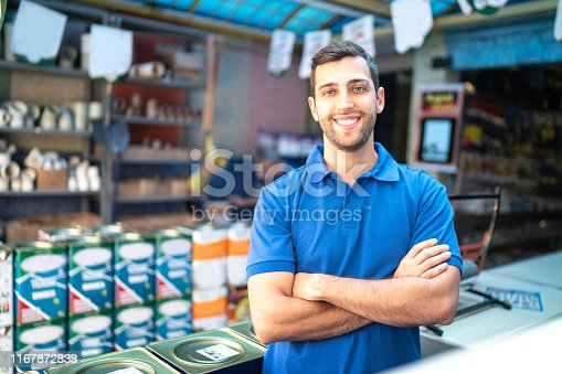 Portrait of a young sales man standing in a paint store