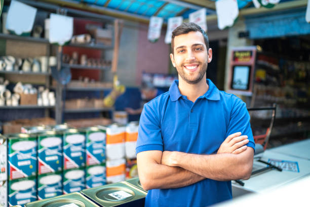 Portrait of a young sales man standing in a paint store Portrait of a young sales man standing in a paint store salesman stock pictures, royalty-free photos & images