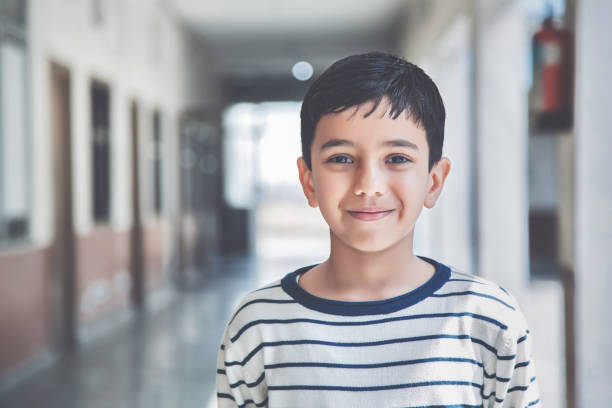 Portrait of a young school boy smiling Close-up portrait of smiling 8-9 years Indian kid, standing straight at school campus in school uniform and looking at camera 8 9 years stock pictures, royalty-free photos & images