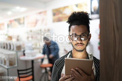 Portrait of a young seller using digital tablet while working in a natural product shop