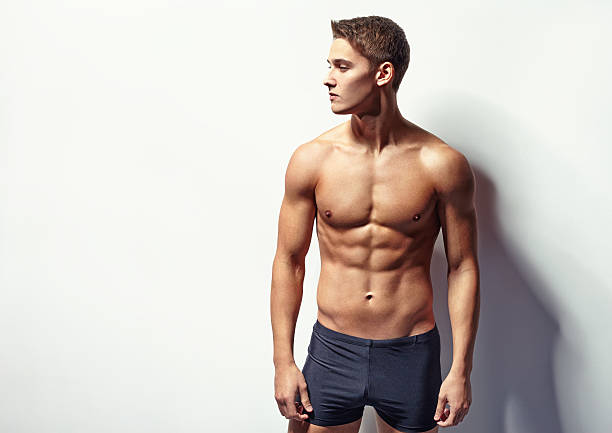 Portrait of a young sexy muscular man Portrait of a young sexy muscular man in underwear looking away against white wall with copy space shirtless male models stock pictures, royalty-free photos & images