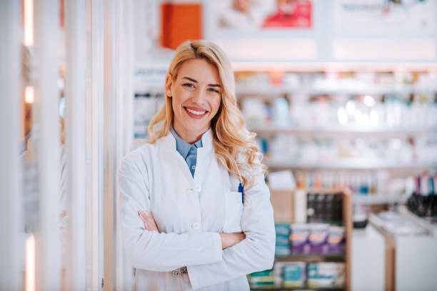 Portrait of a young smiling blonde druggist at work, looking at camera. stock photo