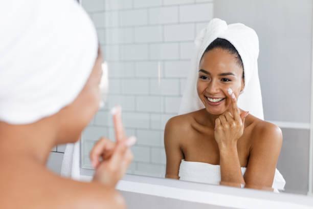 Porträt einer jungen lächelnde Frau anwenden Feuchtigkeitscreme auf ihr Gesicht in das Badezimmer – Foto