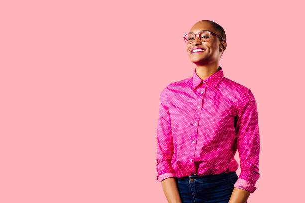 portrait of a young smiling woman in pink shirt, isolated on pink studio background - carlos david stock pictures, royalty-free photos & images