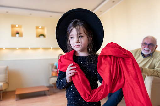 Beautiful Little Girl with Elegant Black Hat and Red Scarf who is Smiling while Standing in the Living Room Inside the House and Feeling Satisfied and Confident.