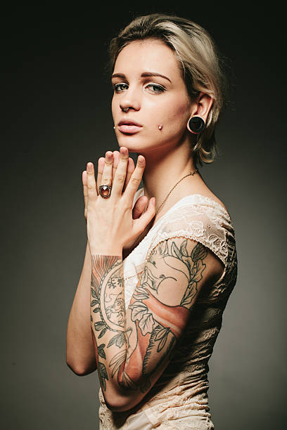 portrait of a young tattooed woman - nose ring stock photos and pictures