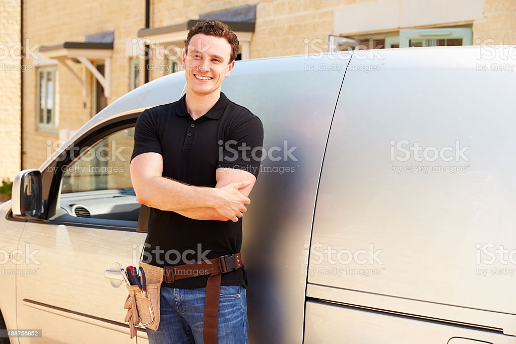 Portrait of a young tradesman by his van stock photo