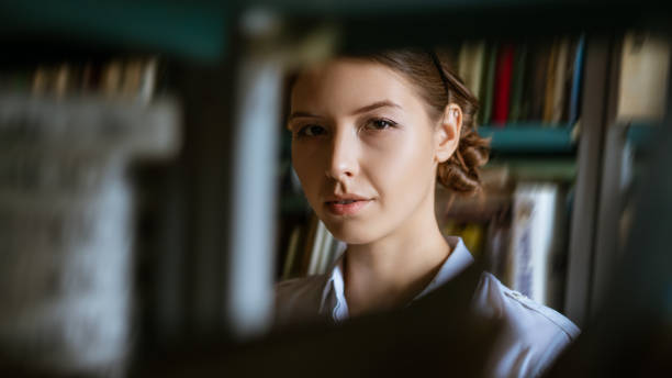 Portrait of a young woman against the background of books in the library, looking through the shelves of books . The concept of preparing for the exams stock photo