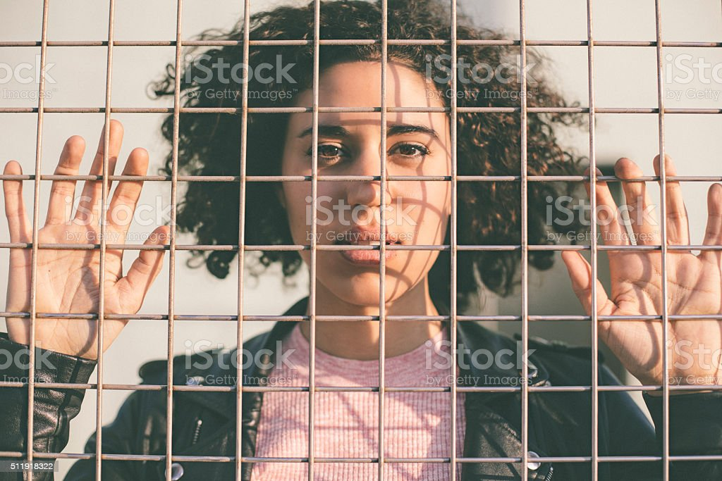 Portrait of a young woman behind a wire mesh stock photo