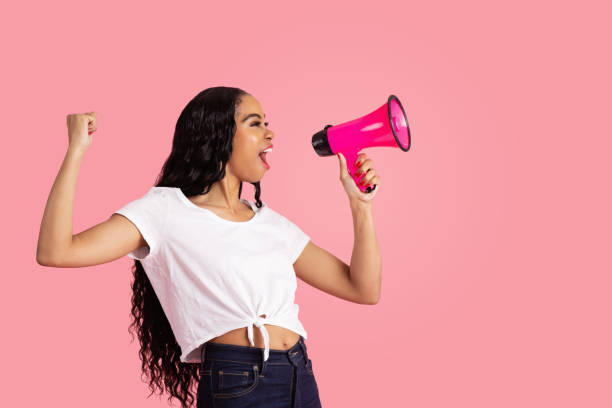 portrait of a young woman being loud and heard by shouting through megaphone with fist up and mouth open - carlos david stock pictures, royalty-free photos & images