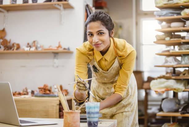retrato de uma jovem mulher, criando a cerâmica, usando laptop - cerâmica artesanato - fotografias e filmes do acervo
