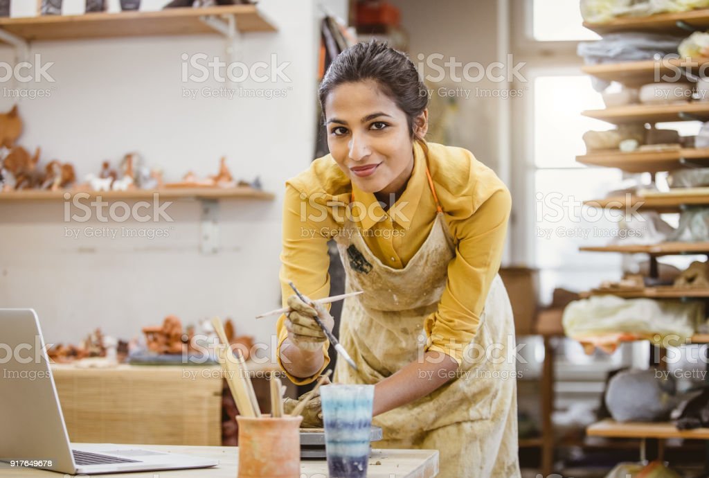 Portrait of a Young Woman Creating Pottery, Using Laptop - foto stock