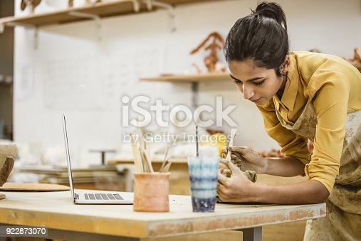 Portrait of a Young Woman Creating Pottery, Using Laptop