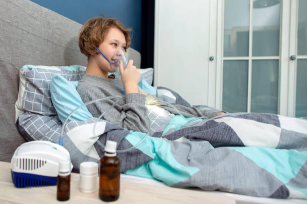 Portrait of a young woman doing inhalation at home. Use nebulizer and inhaler for the treatment. Young woman inhaling through inhaler mask. – zdjęcie