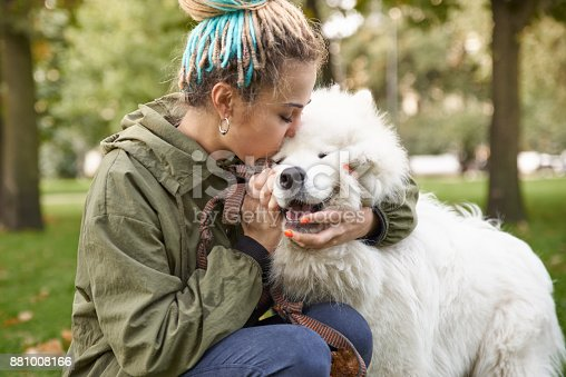 istock portrait of a young woman in a green coat and dreadlocks, kissing with his snow-white Samoyed dog in the autumn Park 881008166