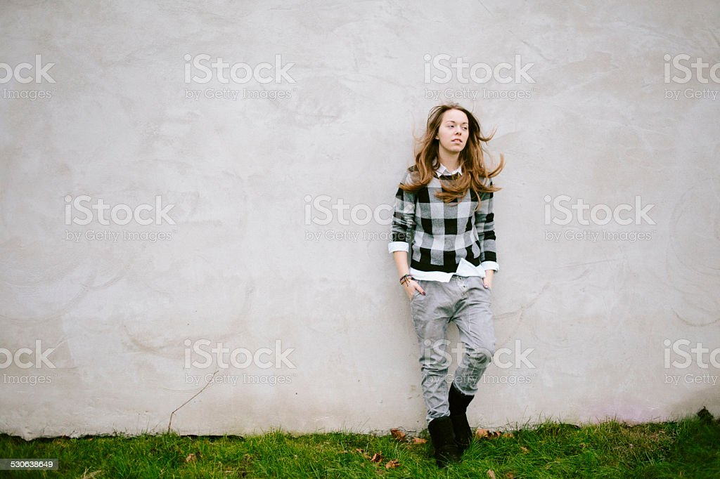 portrait of a young woman in front of a concrete wall stock photo
