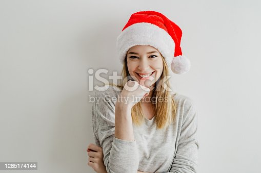 A young smiling woman stands in front of a white wall and has a Santa Claus hat on her head
