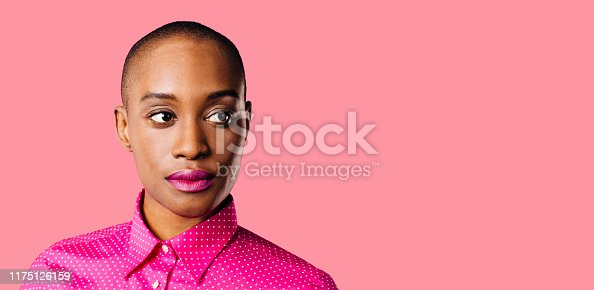 Portrait of a young woman in pink shirt looking to the side, isolated on pink studio background