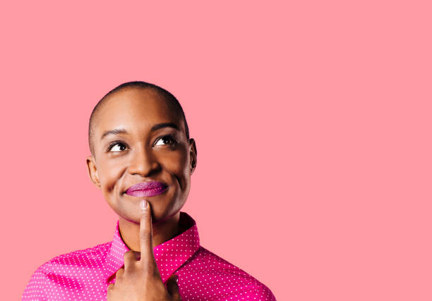 portrait of a young woman in pink shirt with finger on mouth looking up thinking, isolated on pink studio background - carlos david stock pictures, royalty-free photos & images