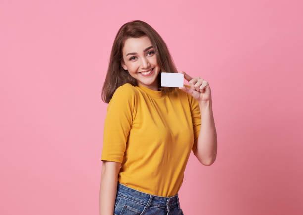 Porträt einer jungen Frau im gelben Hemd mit Kreditkarte und Wegblick auf Kopierraum isoliert über rosa Hintergrund. – Foto