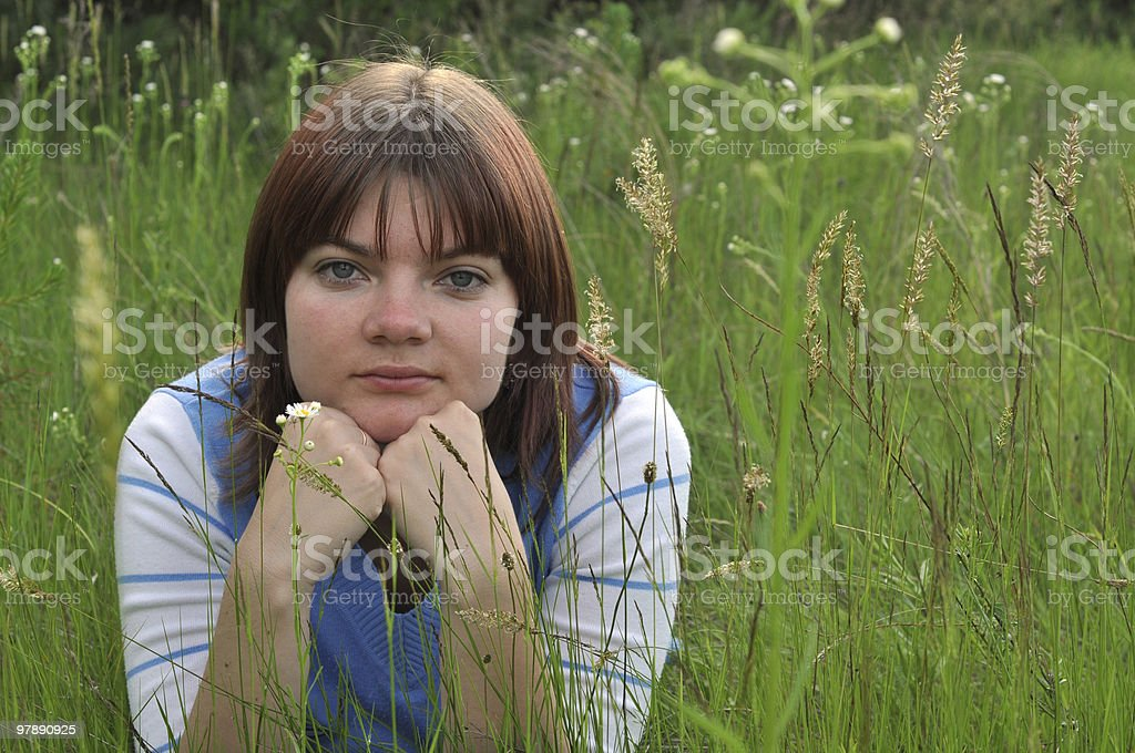 Portrait of a young woman lying in the grass royalty-free stock photo
