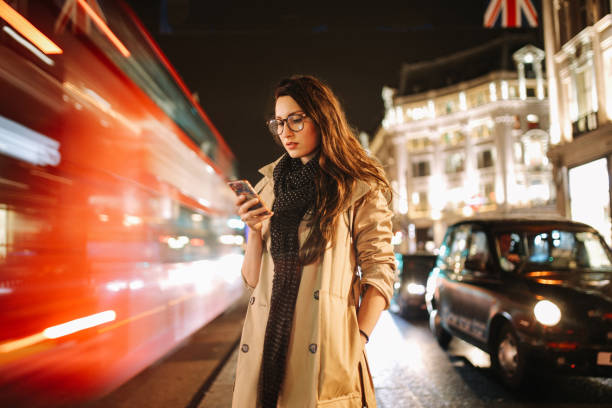 Portrait of a young woman on the busy streets of London downtown in the evening, texting for a cab Vintage toned portrait of a young woman, wearing a trench coat, walking on the busy streets of London in the evening. Going home after work, texting on her cellphone, trying to find Uber or a cab. long exposure stock pictures, royalty-free photos & images