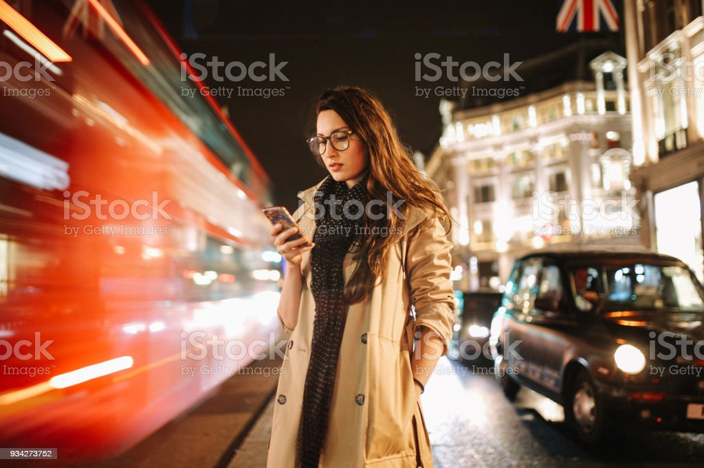 Portrait of a young woman on the busy streets of London downtown in the evening, texting for a cab stock photo