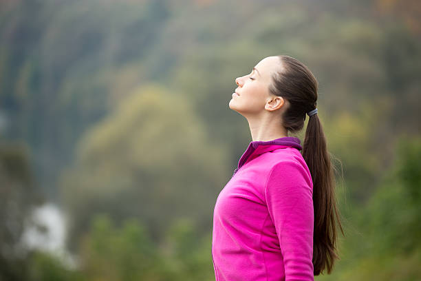 Portrait of a young woman outdoors in sportswear, head up - Photo