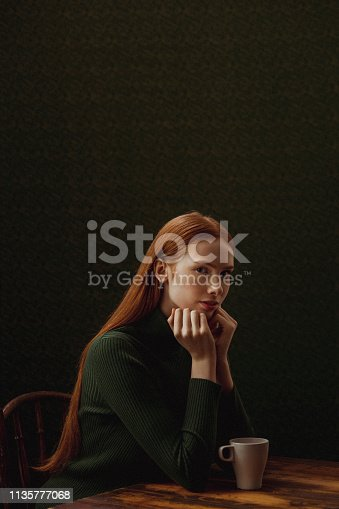 Renaissance style shot of an adolescent girl sitting at a table with a coffee cup and looking at the camera. She is sitting in front of a studio background.
