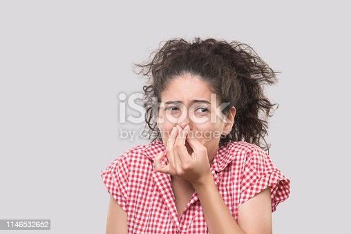 Portrait of a young woman pinching her nose with disgusted facial expression over gray background. Horizontal composition. Studio shot.
