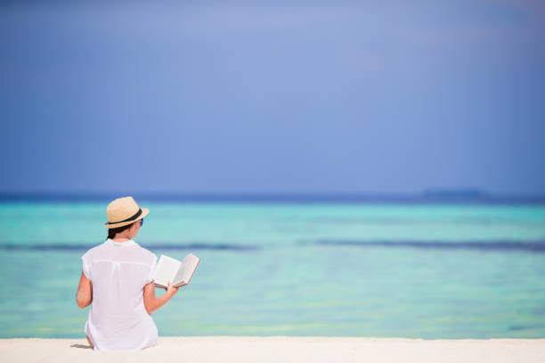 Porträt einer jungen Frau, die sich am Strand entspannt und ein Buch liest – Foto