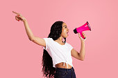 istock Portrait of a young woman shouting through megaphone with arm up and mouth open 1247732972