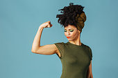 istock Portrait of a young woman showing her arm and strength and loking down 1218015002