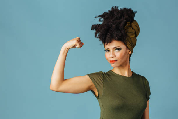 Portrait of a young woman showing her arm and strength Portrait of a young woman showing her arm and strength strong woman stock pictures, royalty-free photos & images