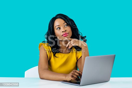 Portrait of a young  woman sitting behind desk and computer laptop, looking up thinking